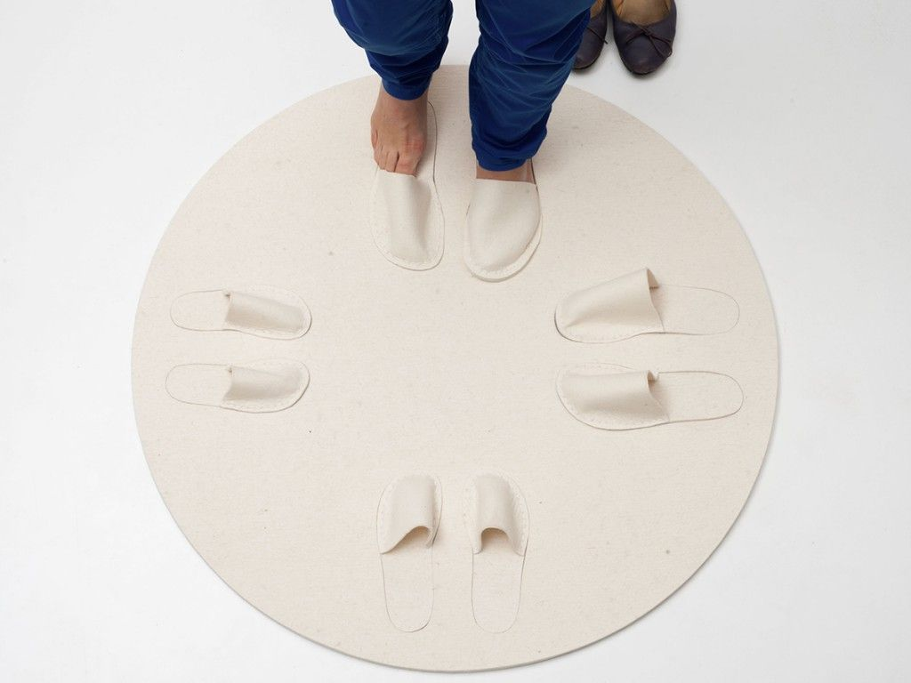 round carpet with four pairs of cut-out slippers arranged like on a clock